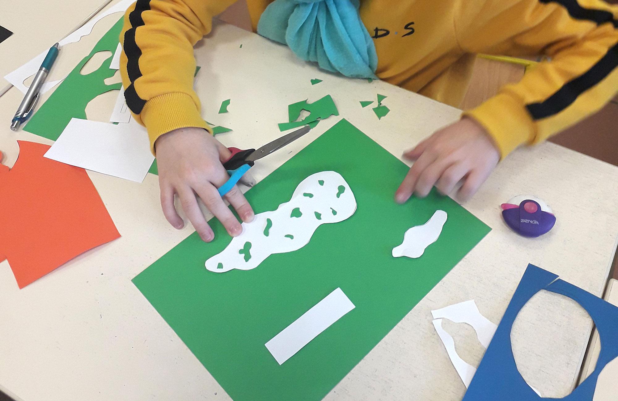 Une petit fille découpe des formes dans des feuilles de couleurs