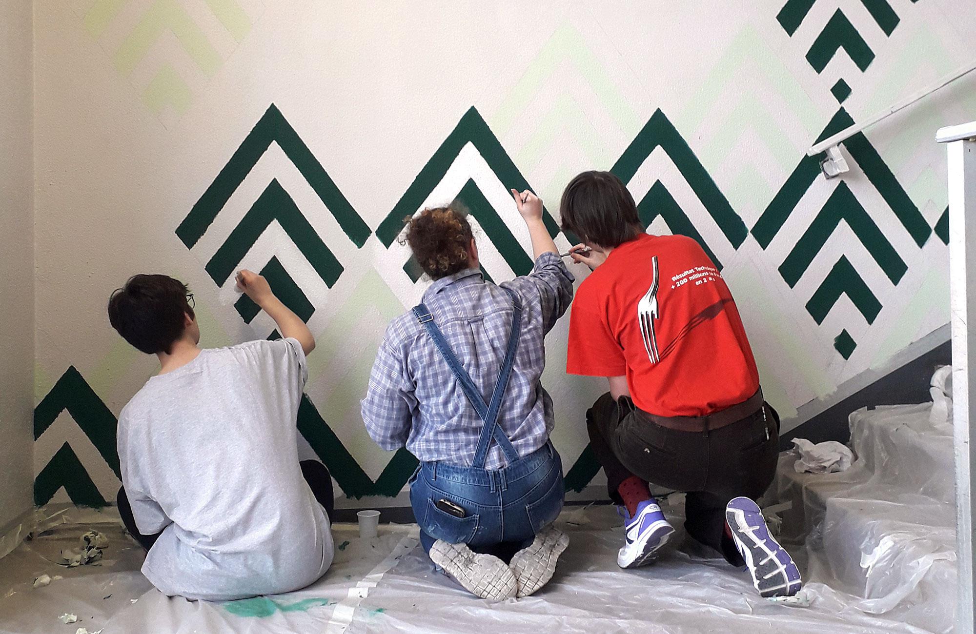Trois étudiantes peignent des formes géométriques sur un mur