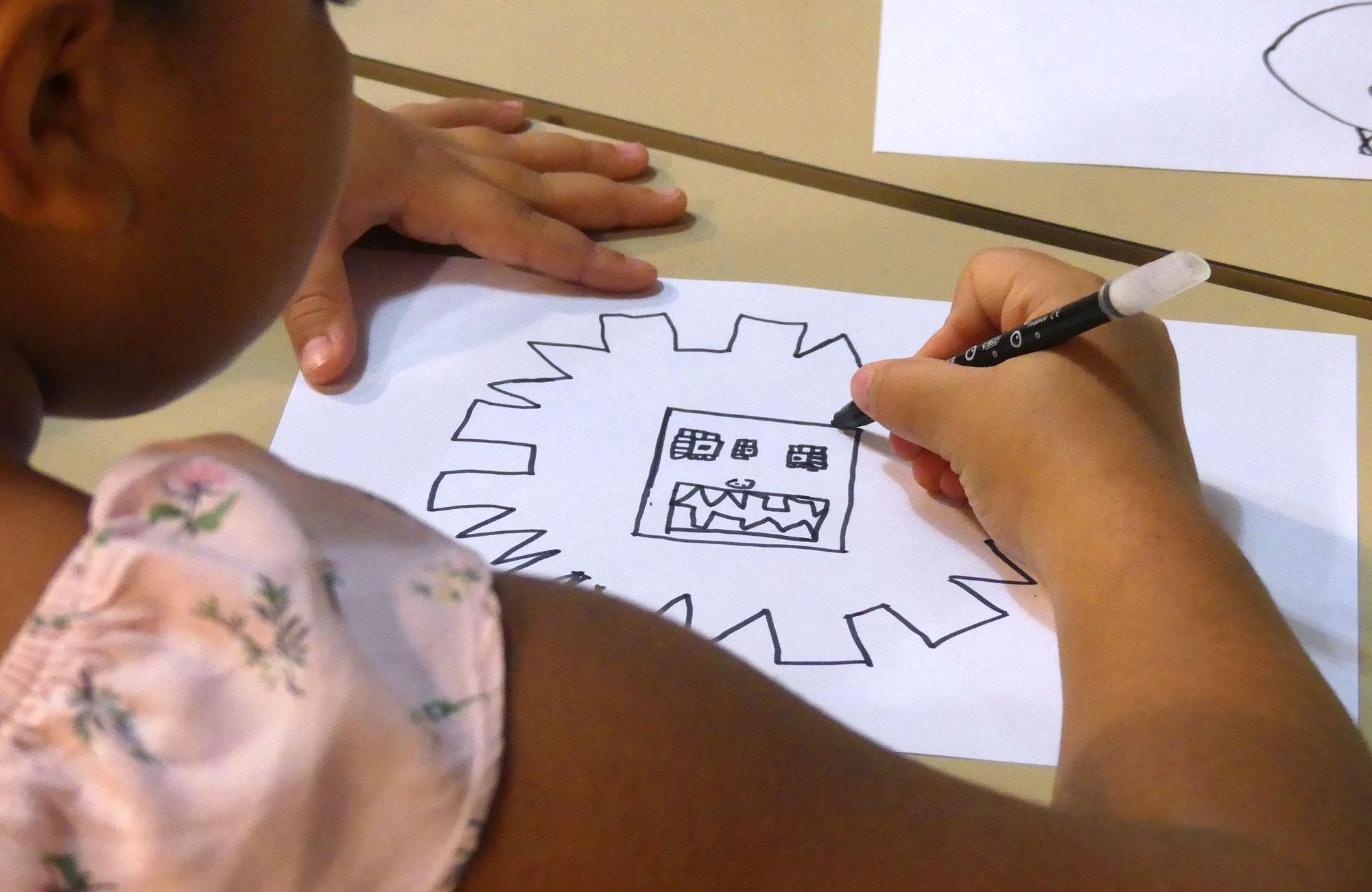 Une petite fille dessine une tête de lion